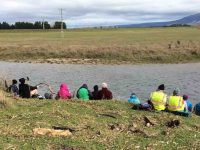 Lunch at the Taieri River. Sheltering as much as possible from the cold Nor-wester.